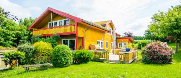 Das gelbe Haus mit rot verziertem Balkon. Im Vordergrund ist die saftige Rasenfläche zu sehen